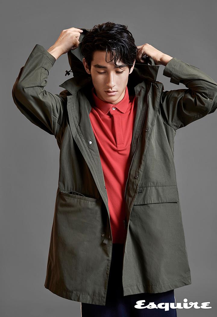 카키 사파리 코트, 레드 폴로 셔츠, 네이비 트랙 팬츠, 모두 라코스테.