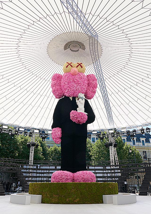 킴 존스는 쇼를 위해 아티스트 KAWS에게 의뢰하여 10m 크기의 디올 맨 슈트를 입은 꽃 조각상을 만들었다.