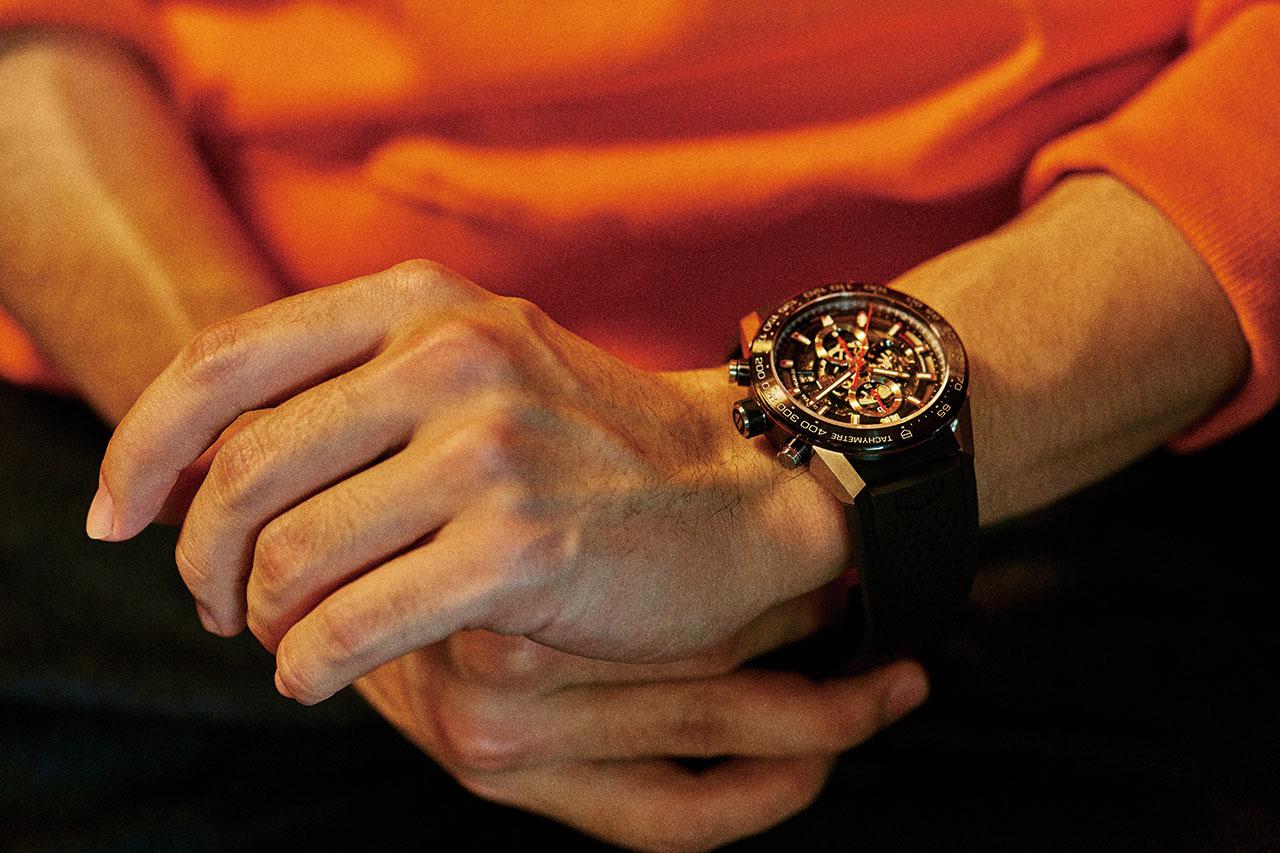 태그호이어 까레라 칼리버 호이어 01 크로노그래프 45mm, 지름 45mm, 모듈러 방식으로 만든 티타늄 케이스, 러버 스트랩. 티타늄으로 케이스를 만들어 크지만 가벼운 시계. 600만원대. 오렌지색 스웨트셔츠 카이아크만, 생지 청바지 코스.