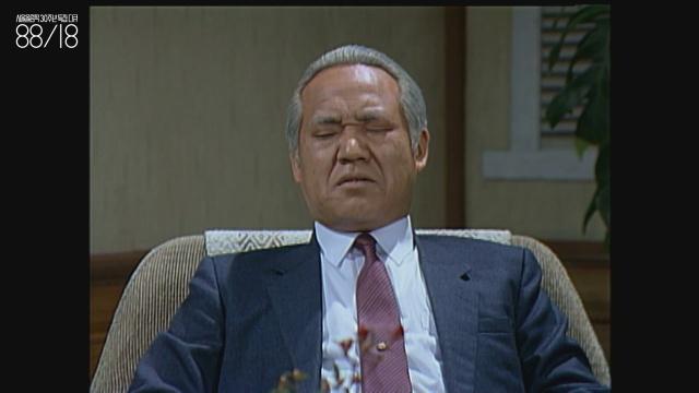 정한용(1954~) 배우. 해당 화면에서 정한용은 30대 정도였을 텐데도 장년층 연기를 하는 중이다. 영상 속 정한용은 정경유착이라는 개념에 대해 이야기하고 있다.
